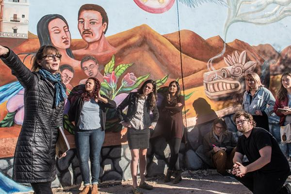 Students stand infront of a painted mural with instructor